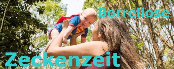 Mutter hält Baby mit Superman-Strampler im Wald hoch,